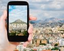 travel concept - tourist taking photo of Athens city skyline on mobile gadget, Greece